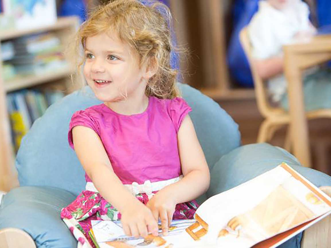 Preschool girl reading a book
