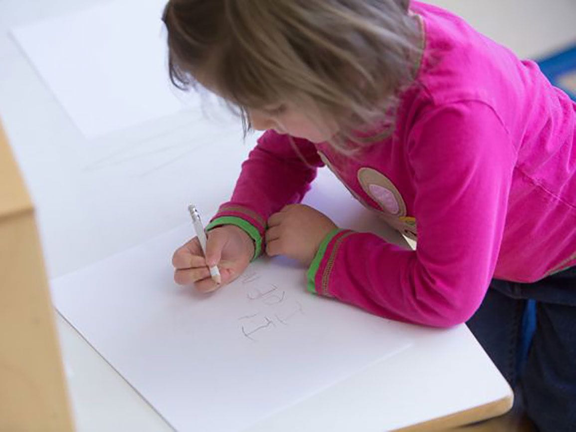 Preschool girl writing on paper