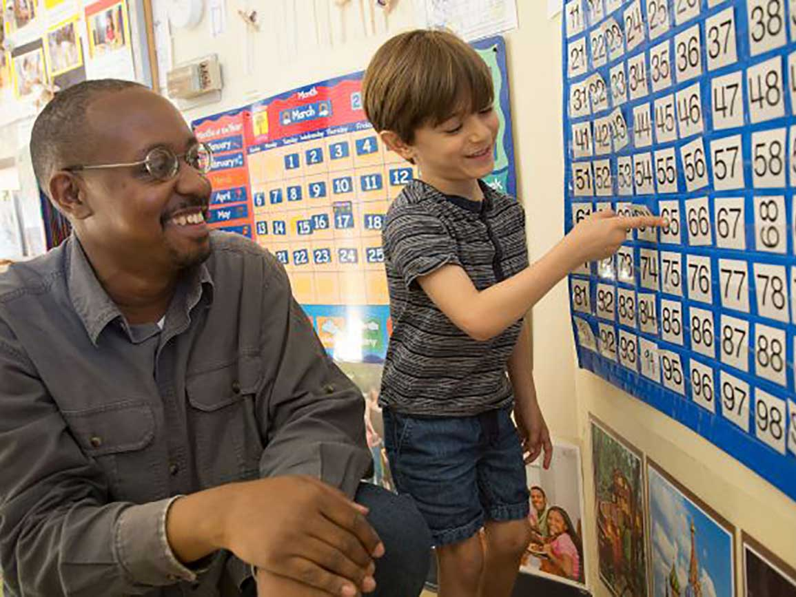 Teacher and boy pointing to calendars