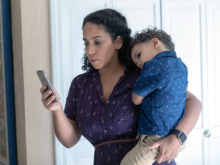 Mom looking at phone while holding child