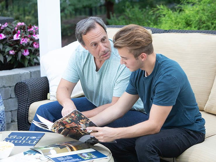 Father and teenage son reviewing college brochures