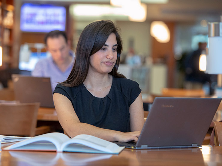 Woman in library working on laptop with textbook open