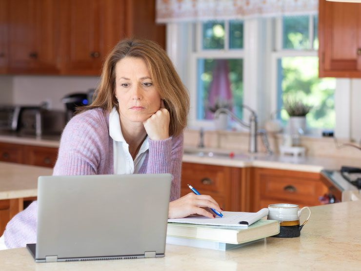 Woman working at laptop in her home kitchen