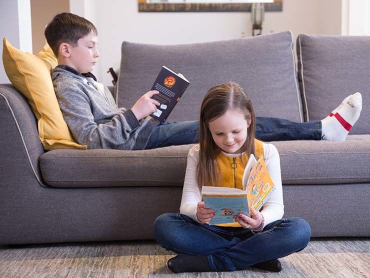 Siblings reading at home on the couch