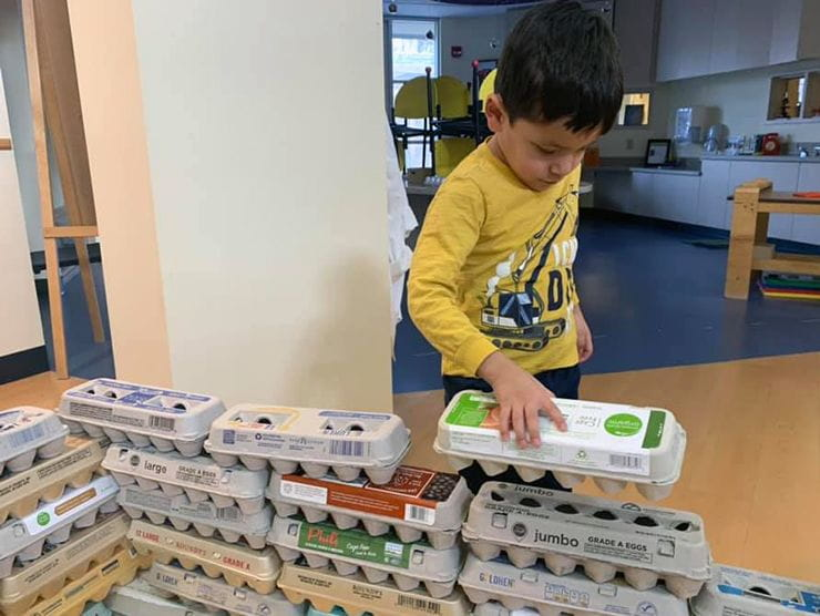 Child building house made out of egg cartons