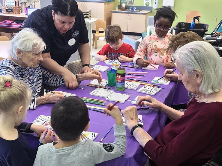 Children and seniors making art together