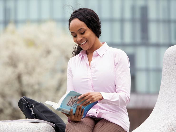 Woman reading nursing textbook outside