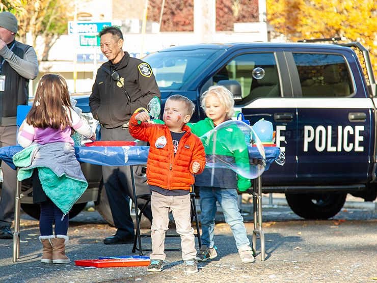Children play in front of a police truck on display at a Bright Horizons fundraiser for a domestic violence shelter.