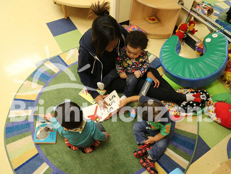 Teacher reading with three Bright Horizons toddlers