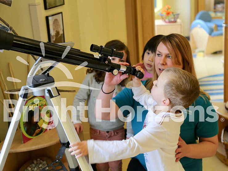 Teacher helping Bright Horizons preschoolers use a telescope