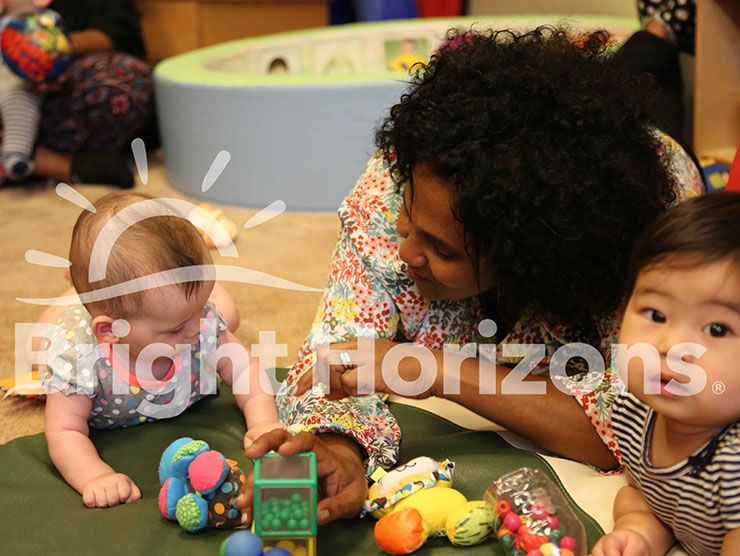 Bright Horizons teacher sitting with infants during tummy time