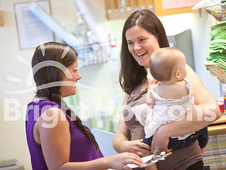 Mom holding her infant while talking to the teacher