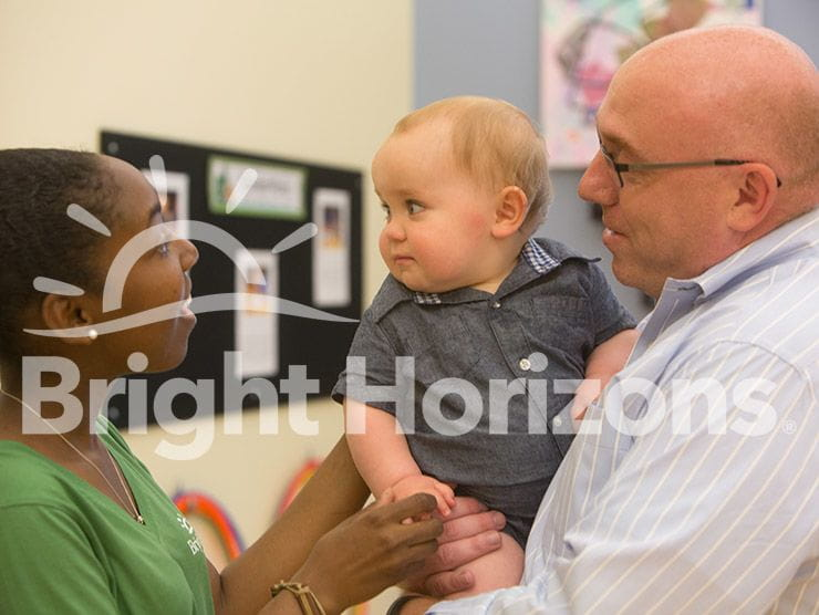 Dad holding his infant son while talking to the teacher