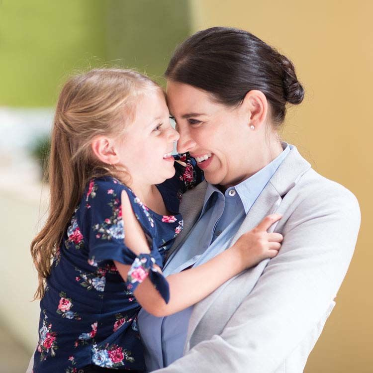 Working mom hugging preschool-aged daughter