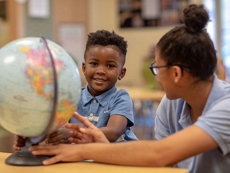A toddler reviewing a globe with his bright horizons child care teacher.