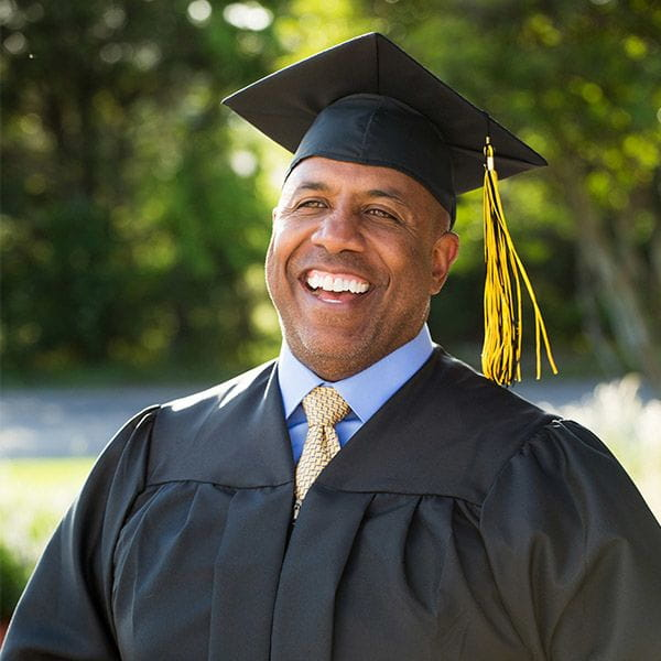 A man wearing a cap and gown for college graduation.