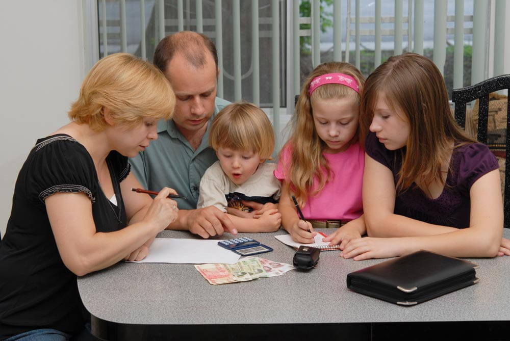 family teaching money skills and financial literacy to kids