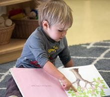 Preschool aged boy on the floor reading a book