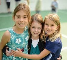 Three school age girls with their arms around each other on the playground