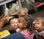 Teacher reading to a group of toddlers