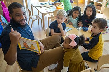 Male teacher reading to a group of preschoolers